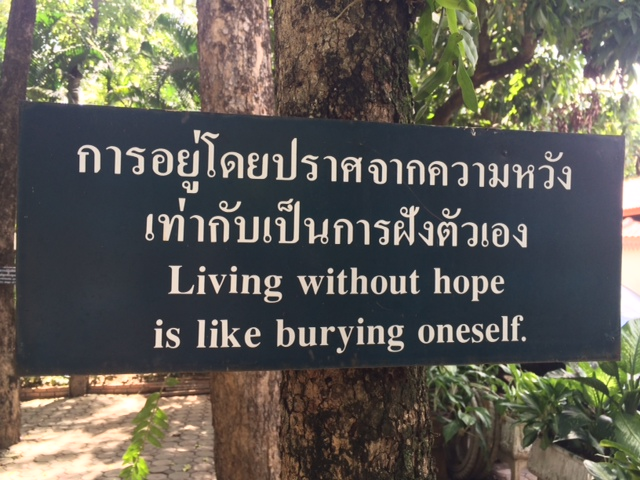 Sign on tree in Thai and English: Living Without Hope Is Like Burying Yourself