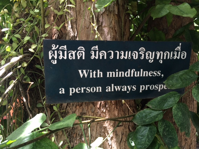 Sign on tree in Thai and English: With Mindfulness, A Person Always Prospers